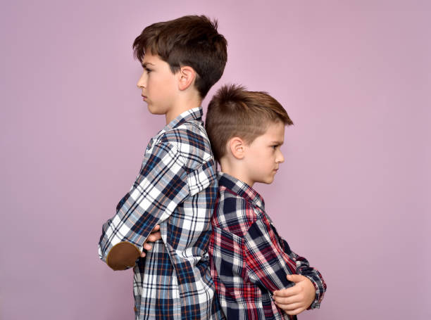 Two angry brothers standing back to back Two angry and frowning brothers standing back to back, not talking to each other brother stock pictures, royalty-free photos & images