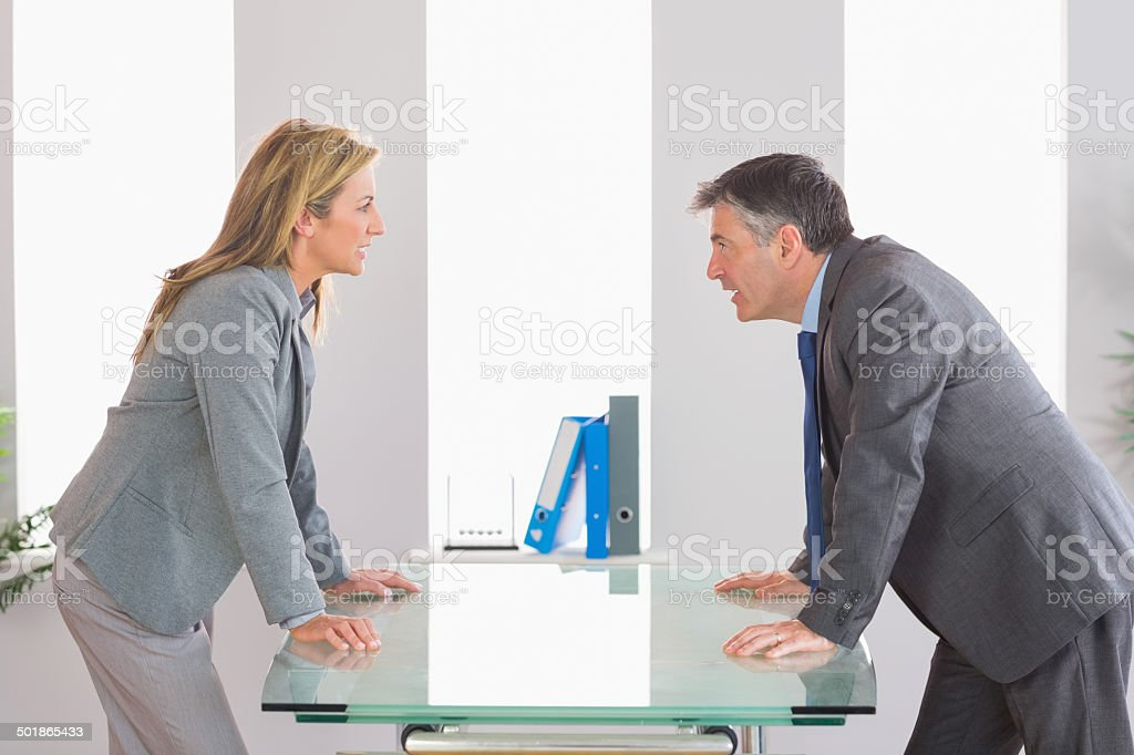 Two angry businesspeople arguing on each side of desk stock photo