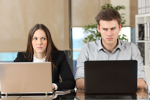 Front view of two angry businesspeople using computers disputing at workplace and looking sideways each other with envy