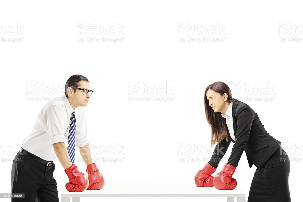 Two angry businesspeople with boxing gloves having an argument stock photo