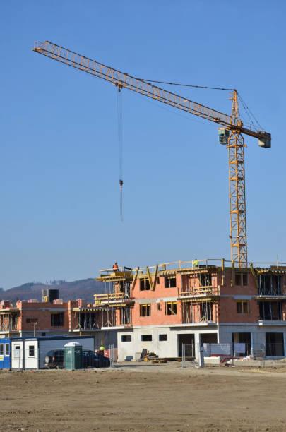 Dos casas de apartamentos en construcción con grúa torre amarilla sobre el sitio de construcción - foto de stock