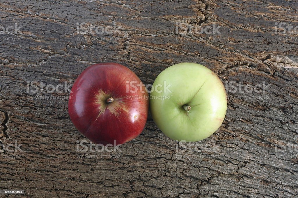 Two apples on a bark piece stock photo
