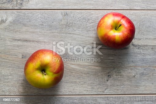 Directly above view of two apples on wooden table. Photo is taken with dslr camera, light comes from bounced flash.