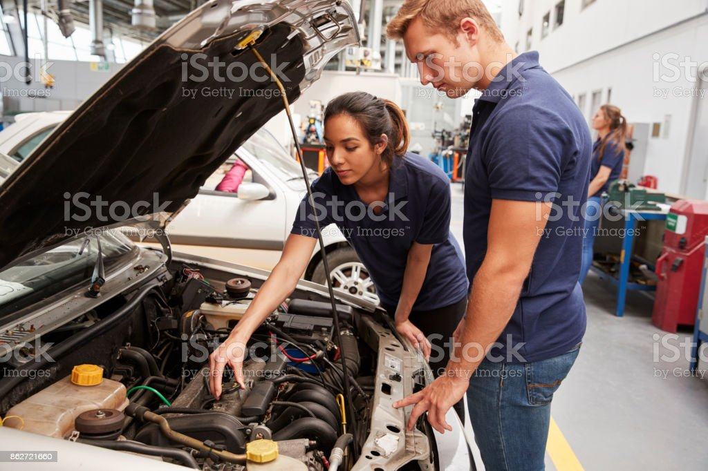 Two apprentice mechanics looking at the engine in a car stock photo