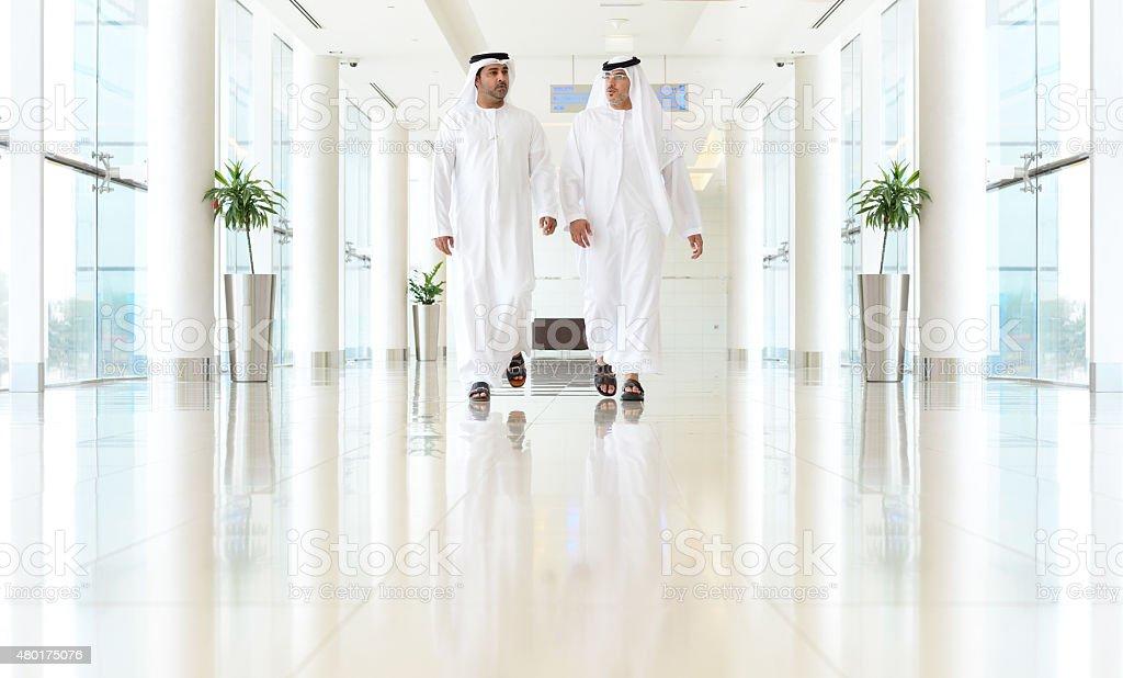Two arab business men walking, talking, meeting stock photo