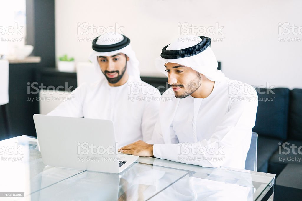 Two Arab Friends Watching Videos on Laptop stock photo