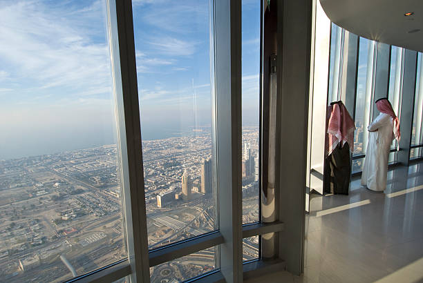 Two Arab men looking over Dubai from the Burj Khalifa Two arab men in traditional dress looking out of the window over Dubai from the Burj Khalifa, the tallest building on earth. burj khalifa stock pictures, royalty-free photos & images
