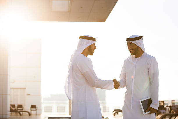 Two Arab Men Shaking Hands Two arab entrepreneurs doing business and shaking hands. One is holding a digital tablet. arabic style stock pictures, royalty-free photos & images