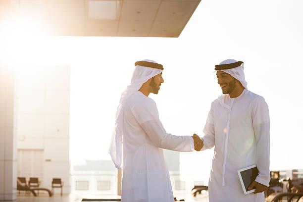 zwei arabische mann händeschütteln - arabeske stock-fotos und bilder