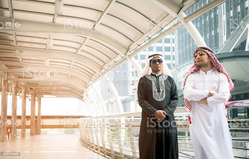 Two Arabian business people standing together in the modern city stock photo