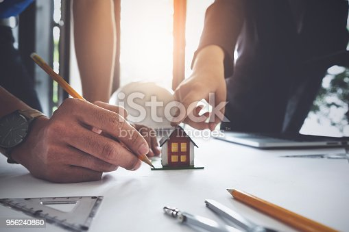 istock Two Architect man consultant working with compasses and blueprints for architectural plan,engineer sketching a construction project concept. 956240860