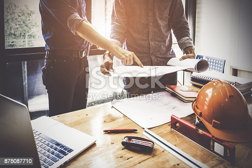 istock Two Architect man working with compasses and blueprints for architectural plan,engineer sketching a construction project concept. 875087710