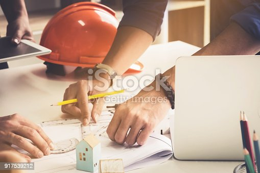 istock Two Architect man working with compasses and blueprints for architectural plan,engineer sketching a construction project concept. 917539212