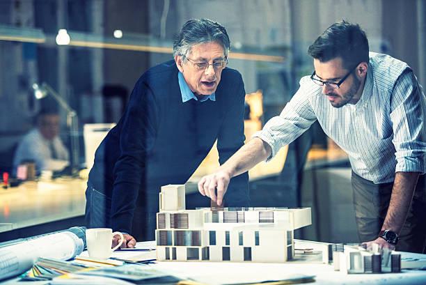 zwei architekten diskutieren neues projekt - architekturberuf stock-fotos und bilder
