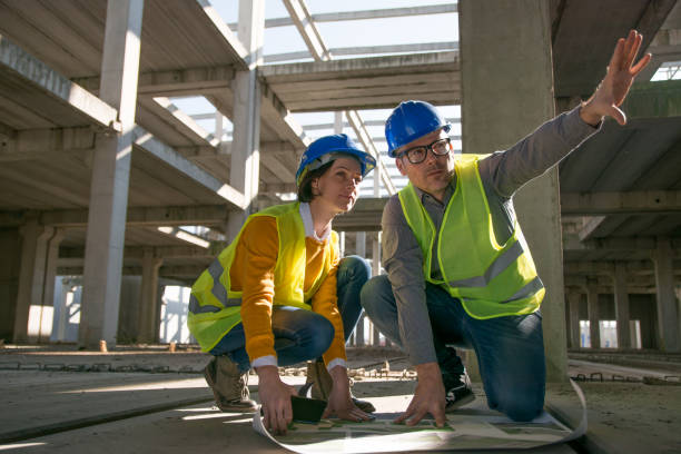two architects kneeling on the floor and discussing over blueprint - civil engineering stock pictures, royalty-free photos & images