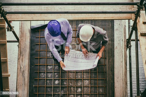 istock Two architects looking blueprint on a construction site 666562666
