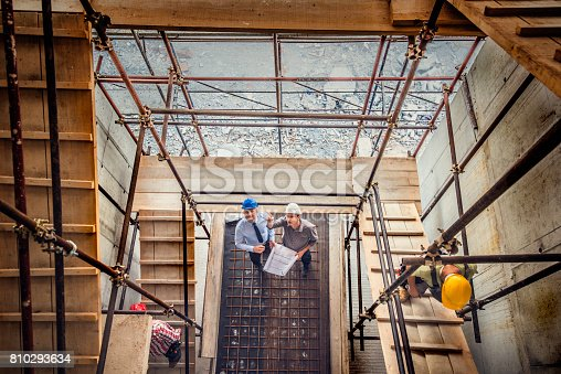 istock Two architects looking blueprint on a construction site 810293634