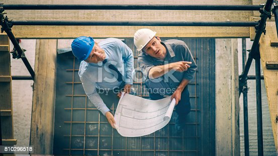 istock Two architects looking blueprint on a construction site 810296518