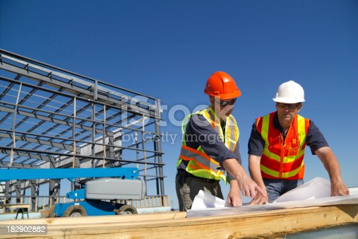 Two construction architects review plans at a construction site.