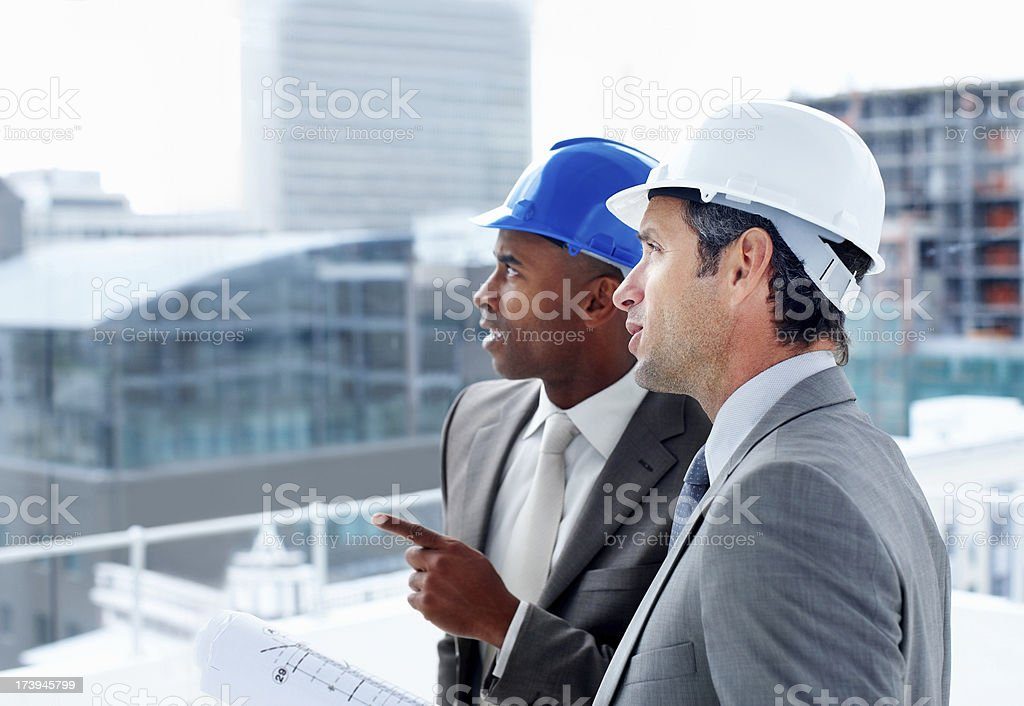 Two architects standing together and planning royalty-free stock photo
