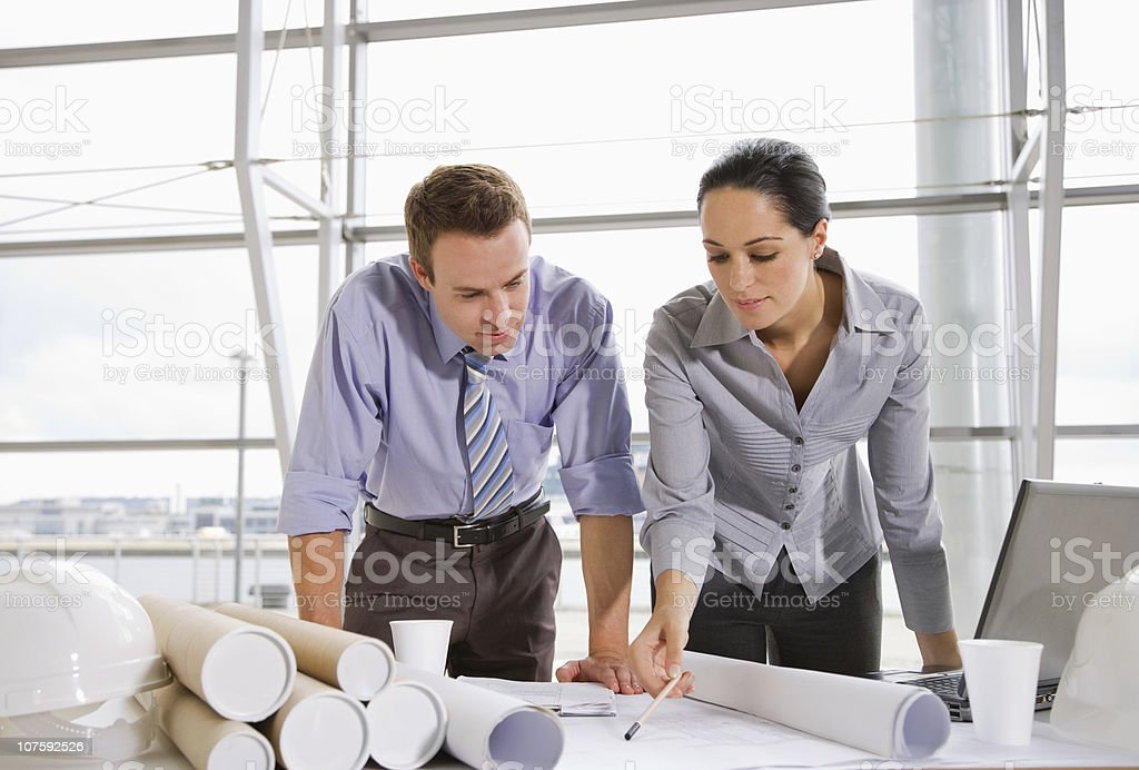 Two architects working on blue prints at office desk