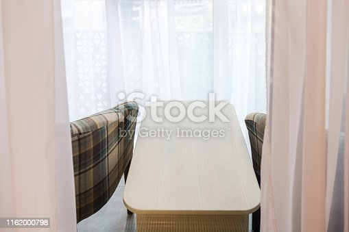 Two armchairs and small coffee table in new house on covered balcony in staging model home or apartment with white curtains blinds