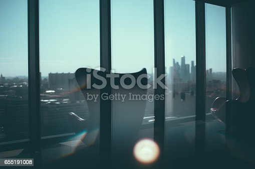istock Two armchairs next to office window 655191008