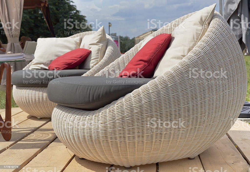 Two armchairs with colored pillows outdoors stock photo