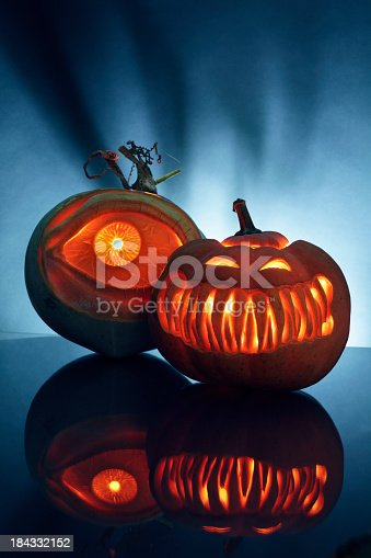 Two carved pumpkin in artistic manner , photo using  urban setting with cold back light and reflection.