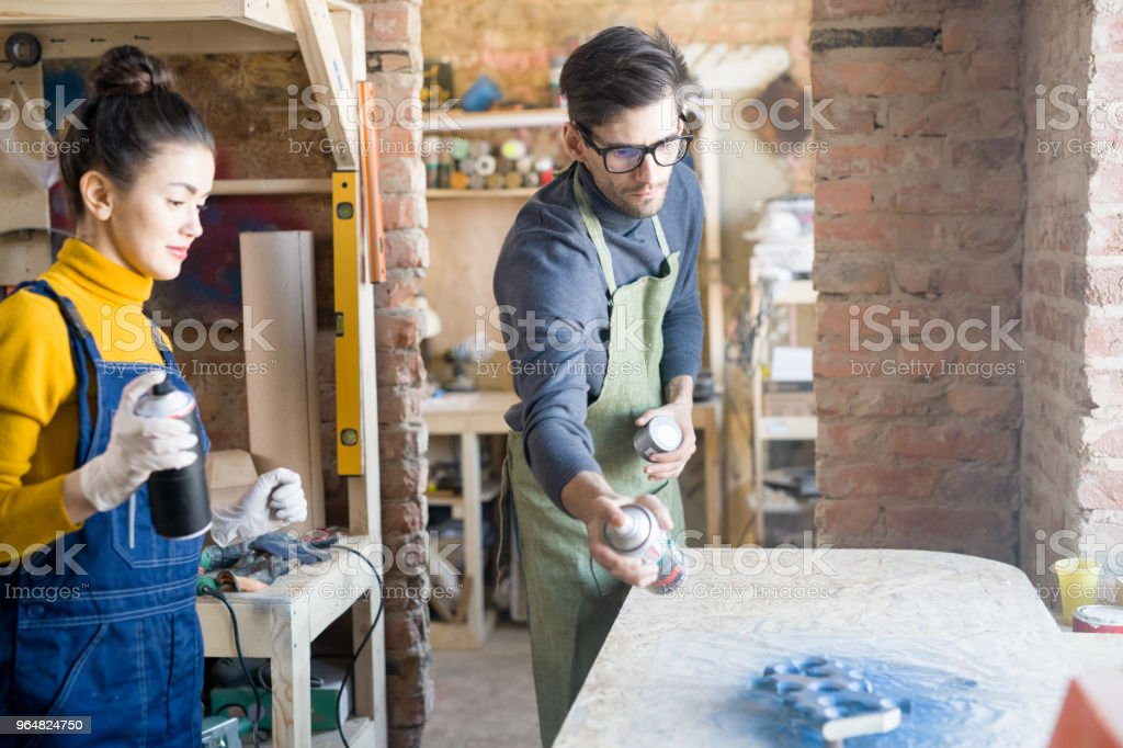 Two Artists Spray Painting Wood royalty-free stock photo