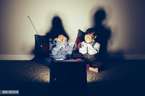 istock Two Ashamed Young Nerds Watching Late Night Television 655182376