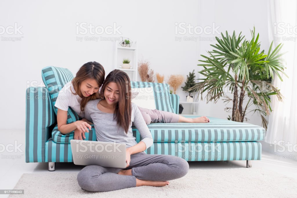 c97e7e136a Duas mulher Ásia usando o computador portátil para compras on-line e  sentado no sofá