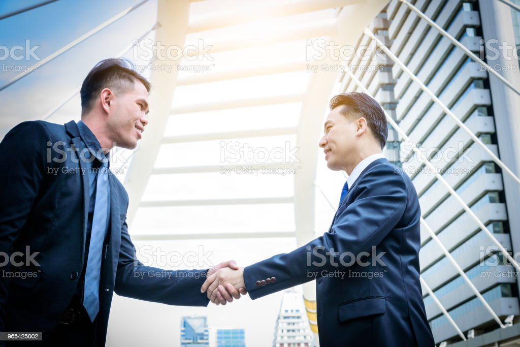 Two asian business have handshake with building and city background. royalty-free stock photo