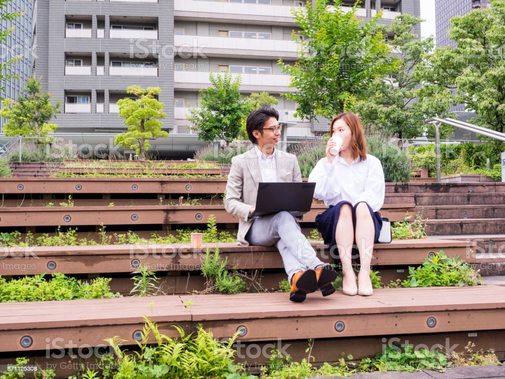 Two Asian business persons are meeting at the park. stock photo