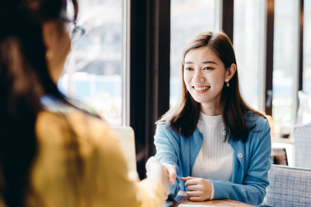 Two Asian businesswomen meeting and shaking hands. stock photo