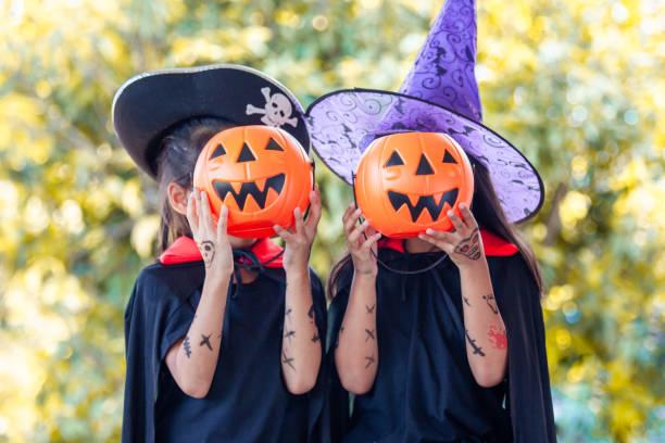 zwei asiatische kinder mädchen in halloween-kostüme und make-up spaß auf halloween-feier - piratenparty snacks stock-fotos und bilder