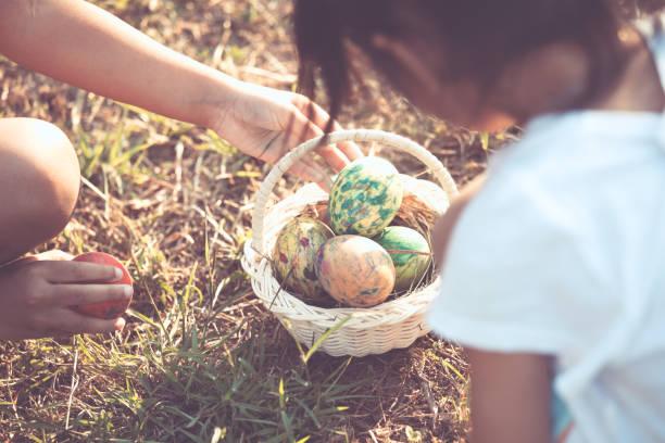 zwei asiatische kind mädchen spielen und sammeln bunte ostereier im korb zusammen im aussenbereich - schöne osterbilder stock-fotos und bilder