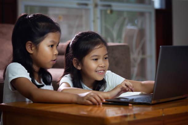 Zwei asiatische Kindermädchen, die Notebook verwenden, um gemeinsam Online-Technologie zu lernen. – Foto