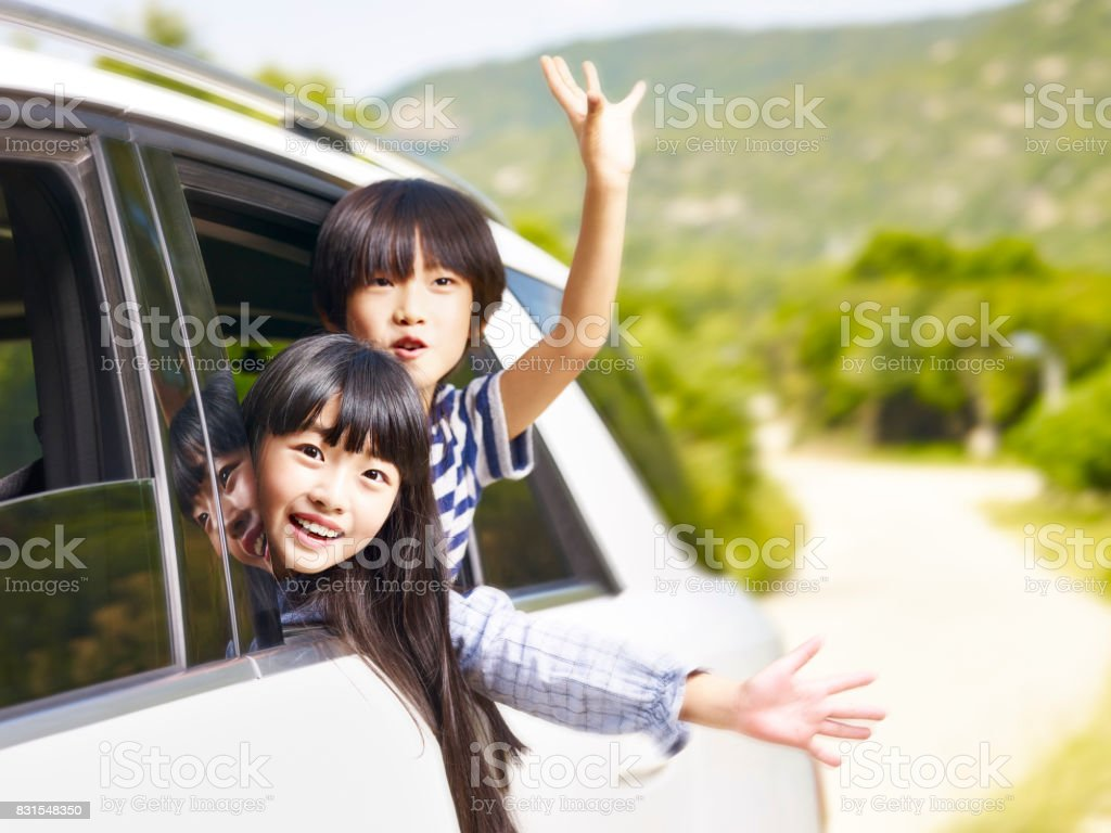 two asian children waving hands while traveling by car stock photo