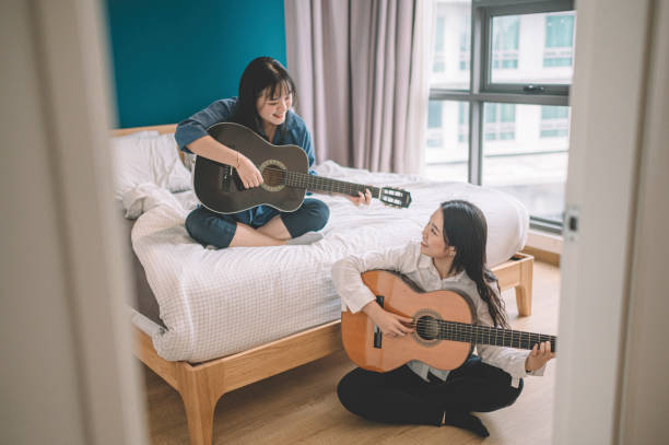 two asian chinese female friends sister  playing guitar in her bedroom during weekend on her bed leisure time two asian chinese female friends sister  playing guitar in her bedroom during weekend on her bed leisure time girl bedroom stock pictures, royalty-free photos & images