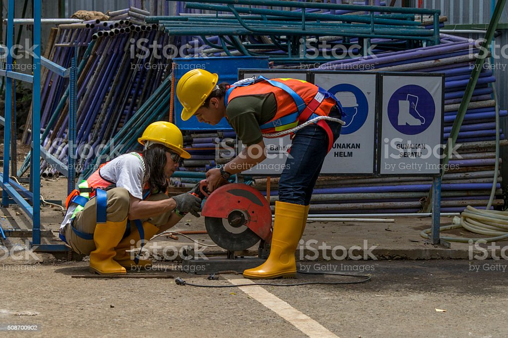 two asian construction workers with safety equipments attached stock photo