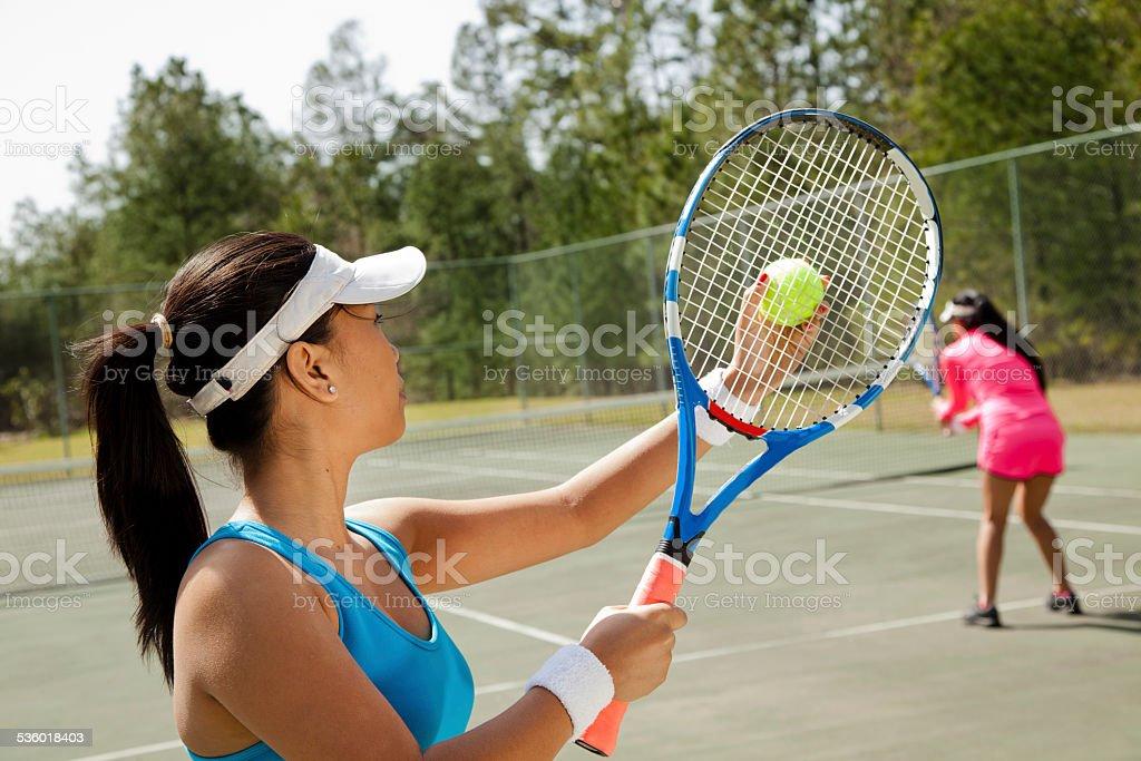 Two Asian descent women friends enjoy game of tennis. Court. stock photo