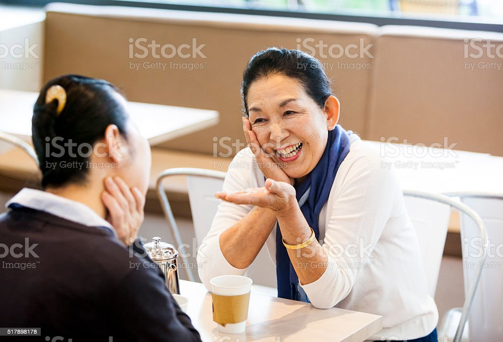Two Asian Elderly Women Telling Jokes To Each Other stock photo