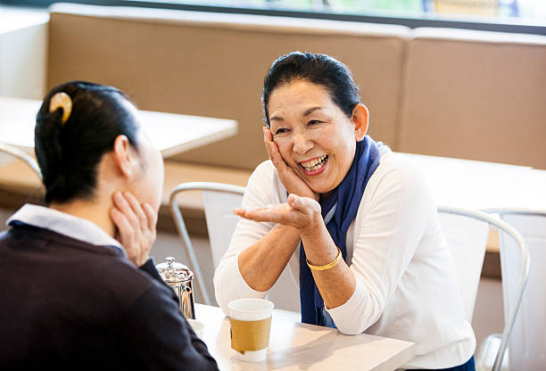 Two Asian Elderly Women Telling Jokes To Each Other stock photo