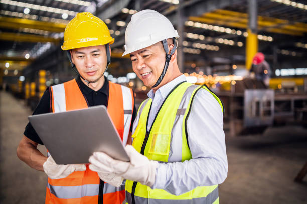 Two Asian engineers using a laptop in a factory stock photo