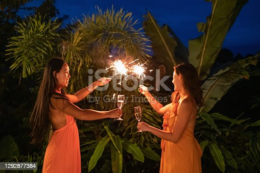 Portrait shot of two Asian friends toasting champagne while playing sparklers during new year's eve celebration in tropical resort