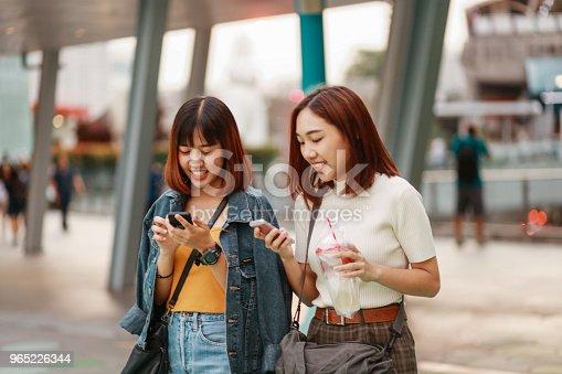 Two Asian Girls In Bangkok Looking At Their Smartphones Chatting About Social Media - Stockowe zdjęcia i więcej obrazów Azja