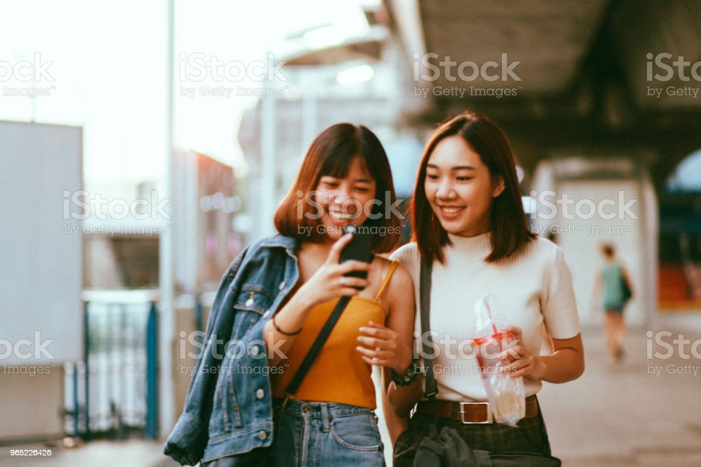 Two Asian girls in Bangkok, looking at their smartphones, chatting about social media stock photo