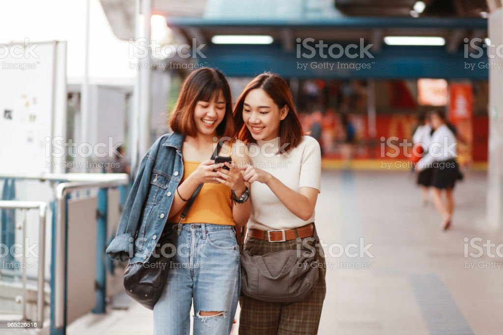Two Asian girls in Bangkok, looking at their smartphones, chatting about social media zbiór zdjęć royalty-free