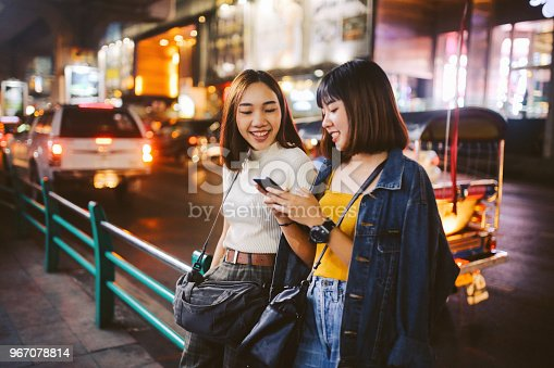 Vintage toned image of two young, Asian women, walking together, chatting, near Siam station on Bangkok Sukhumvit line. They're wearing casual street style clothing, enjoying an afternoon together, texting on their cellphones.